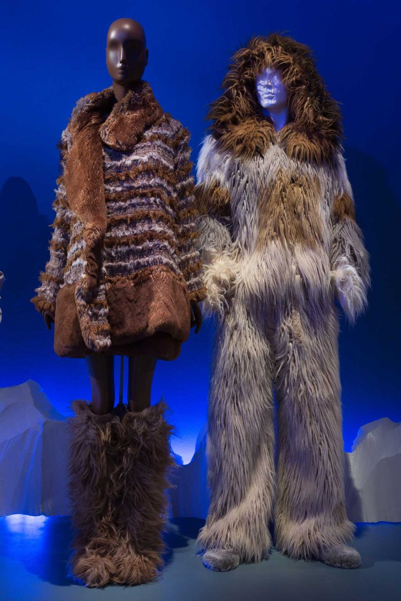 From left: Tweed and faux fur suit by Karl Lagerfeld for Chanel, Autumn/Winter 2010; man's faux fur ensemble by Karl Lagerfeld for Chanel, Autumn/Winter 2010. Both lent by Chanel Patrimoine Collection, Paris