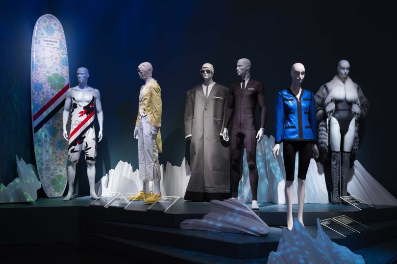 From left: Thom Browne singlet and surfboard; Thom Browne man's suit; Thom Browne oversized wetsuit ensemble; Thom Browne trompe l'oeil wetsuit - all Spring/Summer 2017 and all lent by Thom Browne. Karl Lagerfeld for Chanel, sequin jacket, Spring/Summer 1991. Ohne Titel, neoprene bodysuit, Spring/Summer 2015; Ohne Titel fur, leather, and faux fur coat, Autumn/Winter 2012; and Ohne Titel knit and leather boots, Autumn/Winter 2016. All gifts of Ohne Titel